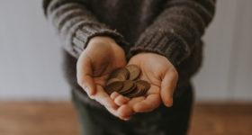 Münzen in ausgestreckten Händen - Taschengeld während eines High School Aufenthaltes in Kanada